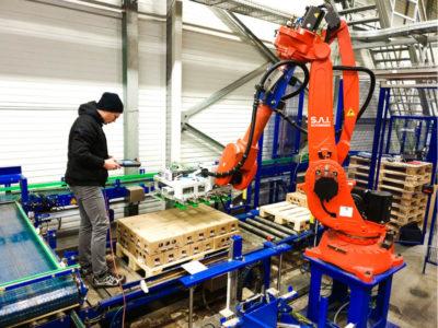 Mitarbeiter S.A.I. programmiert Abstapelanlage in einer Molkerei