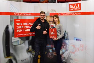 zwei Mitarbeiter der S.A.I. Schweiger GmbH vor der Messewand des Unternehmens