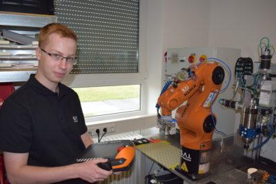 Mitarbeiter bei der Bedienung eines Industrieroboters