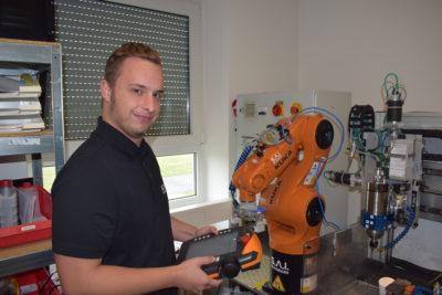 Neuer Praktikant bei der Bedieunung des Schulungsroboters