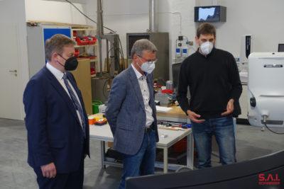 MdL Josef Zellmeier und Bayerns Wissenschaftsminister Bernd Sibler werden von Geschäftsführer Reinhard Schweiger über die Möglichkeiten der Automatisierung für das Beladen von Fräsmaschinen informiert.